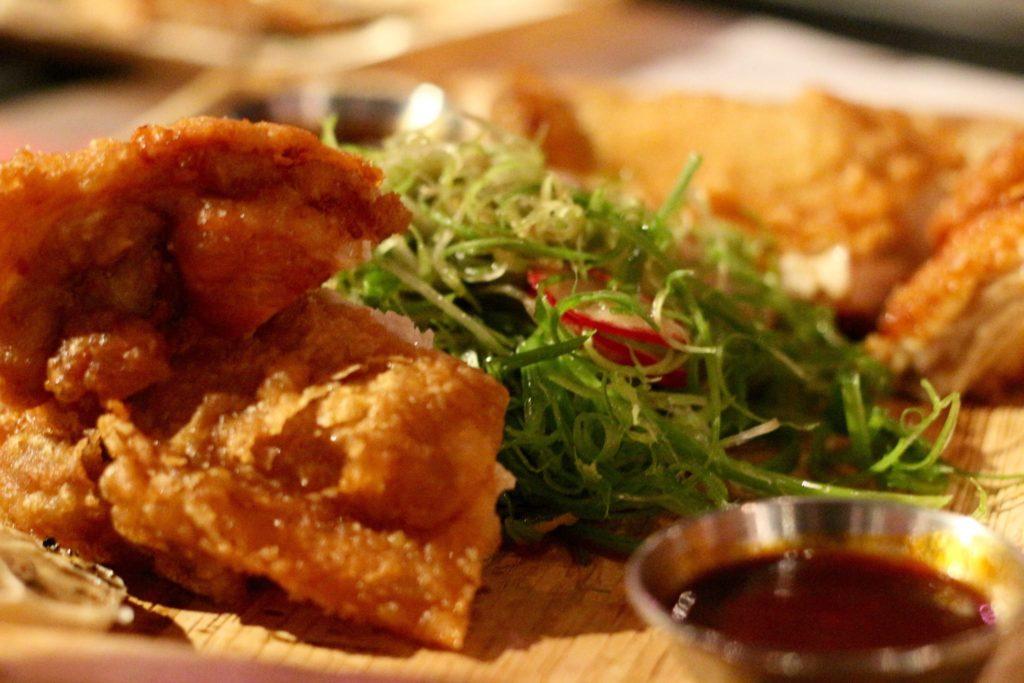 Korean fried chicken with roast garlic heads and scallion salad.